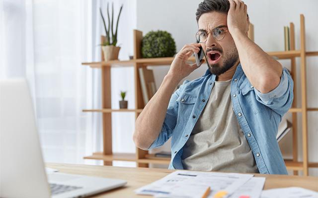 Mann sitzt am Tisch vor dem Laptop und seinem Unterlagen. Er telefoniert aufgeregt auf der Suche nach einem neuen Stromanbieter.