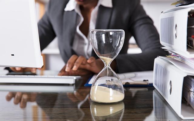 Frau im Büro am Schreibtisch sitzend. Neben Aktenordnern steht eine Sanduhr aus Glas