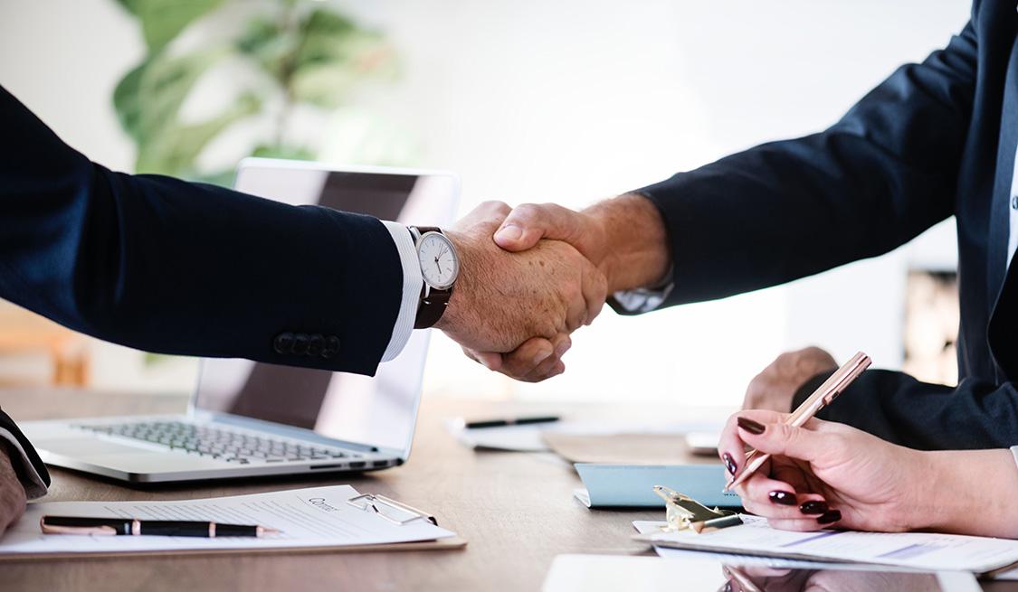 Handschlag zweier Männer im Anzug am Tisch sitzend. Hand einer Frau, einen Stift haltend sitzt daneben. Auf dem Tisch liegen Laptop, Unterlagen und Kugelschreiber