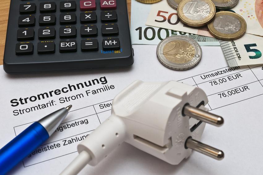 Stromrechnung mit Stift, Taschenrechner und Bargeld danebenliegend