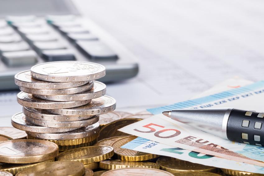 Gestapelte Geldmünzen und Scheine