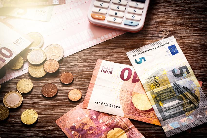 Banknoten, Münzen und ein Taschenrechner