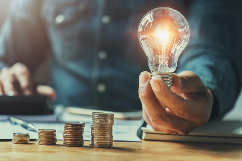 Mann hält eine Glühbirne in der Hand, während er in einen Taschenrechner tippt