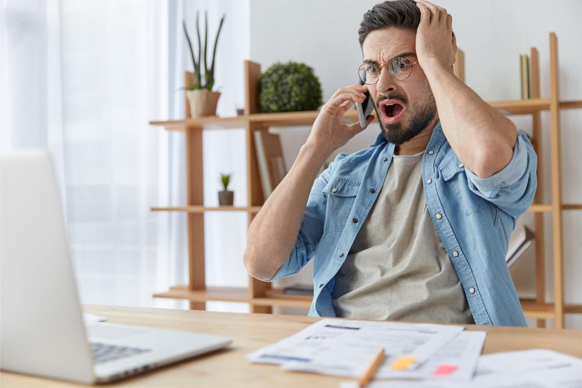Mann mit Bart und Brille schaut entsetzt auf seinen Laptop, während er telefoniert. Sein Stromanbieter hat die Preise erhöht